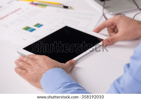 Young businessman working with modern devices, digital tablet and computer