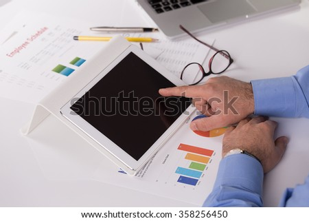 Young businessman working with modern devices, digital tablet and laptop computer - stock photo