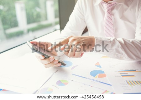Young businessman working with modern devices, smart phone or mobile phone. - stock photo