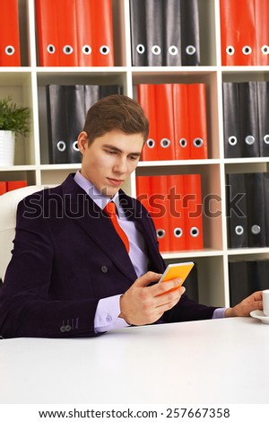 Young businessman writing a message on his smartphone - stock photo