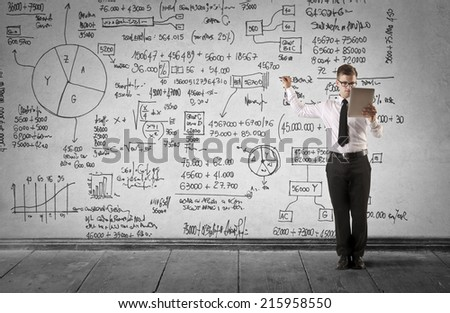 Young businessman writing formulas - stock photo