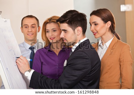 young businessman writing on cardboard, with three colleagues smiling, around him - stock photo