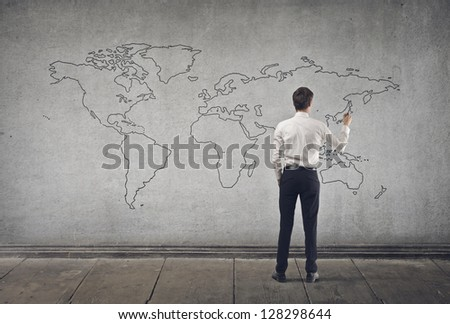 young businessman writing on map - stock photo