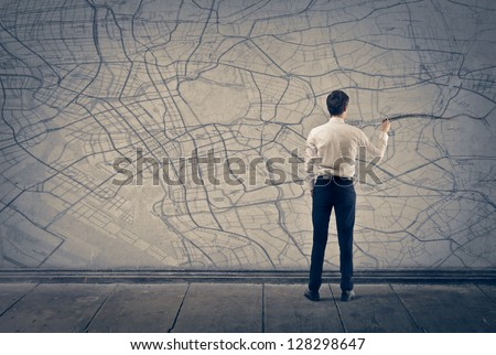 young businessman writing on map