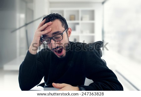 young businessman yawning at work in office  - stock photo