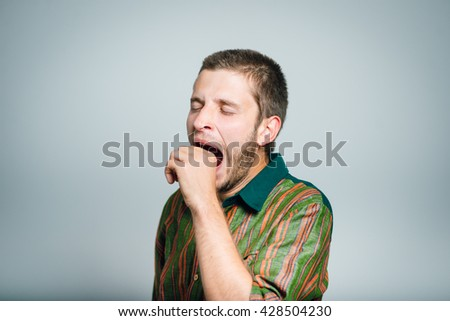 young businessman yawning isolated on a gray background