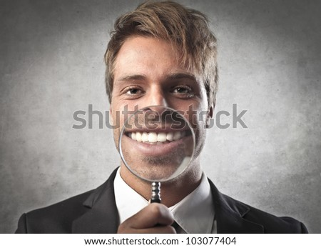 Young businessman zooming on his smile with a magnifying glass - stock photo