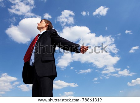 young businessmanin a blue suit embracing air against blue sky