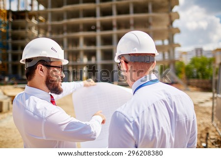 Young businessmen discussing sketch of new building