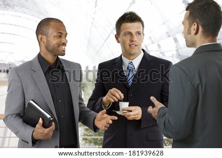 Young businessmen having coffee-break at office lobby, talking, drinking coffee. - stock photo