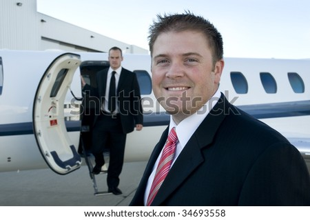 Young businessmen in front of their corporate jet. Focus on the man in front. - stock photo