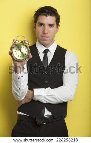 young businessmen on yellow background holding alarm clock stressed out by deadline - stock photo