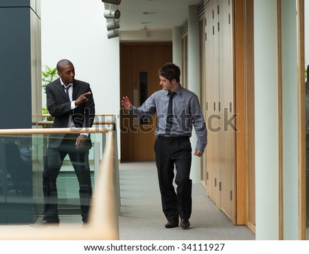 Young businessmen saying goodbye in a corridor - stock photo