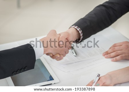Young businessmen shaking hands with each other in the business center. Successful businessmen on a corporate meeting close-up view