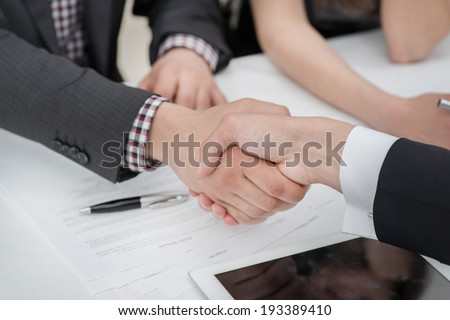Young businessmen shaking hands with each other in the business center. Successful businessmen on a corporate meeting close-up view - stock photo