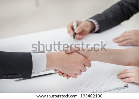 Young businessmen shaking hands with each other in the business center. Successful businessmen on a corporate meeting. Female hand shakes man's hand close-up view