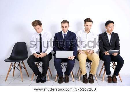 Young businessmen sitting on a chair and using devices in white hall - stock photo