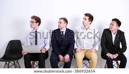 Young businessmen sitting on a chair in white hall
