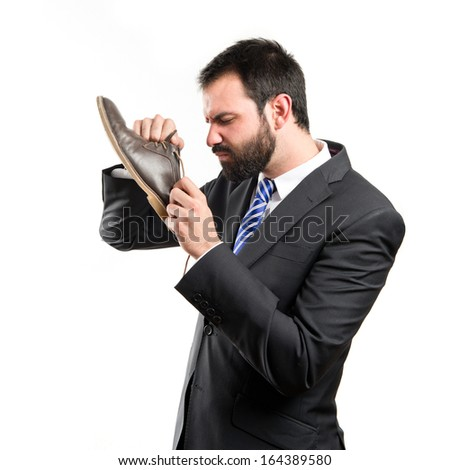 Young businessmen smelling his shoes over isolated background.  - stock photo