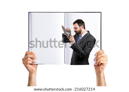 Young businessmen smelling his shoes printed on book - stock photo