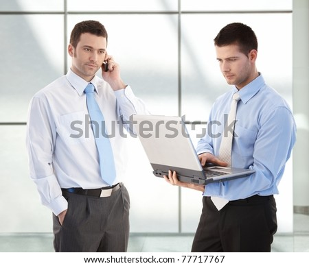 Young businessmen standing in office lobby, one on phone, the other working on laptop.? - stock photo