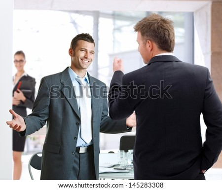Young businessmen talking at meetingroom, smiling happy. - stock photo