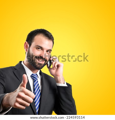 Young businessmen talking to mobile over yellow background.  - stock photo