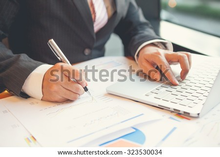 Young businessmen using Notebook and writing business plan at meeting in office