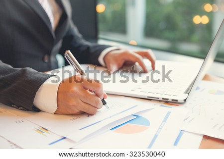 Young businessmen using Notebook and writing business plan at meeting in office - stock photo