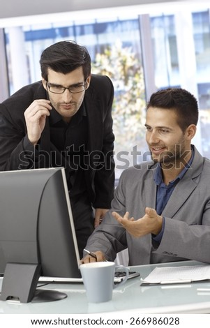 Young businessmen working together, using computer in bright office. - stock photo