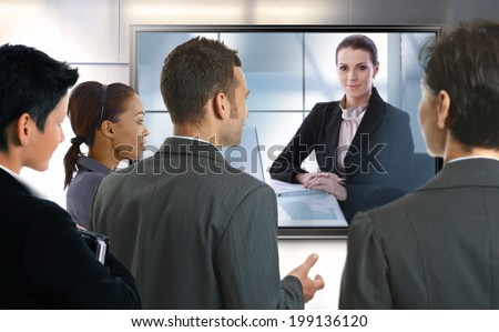 Young businesspeople and businesswoman having video call at office. LCD display.