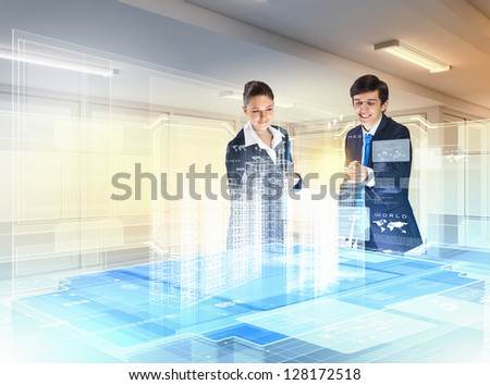 young businesspeople clicking on icon of high-tech image - stock photo