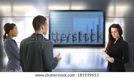 Young businesspeople discussing business results, standing front of big LCD screen.