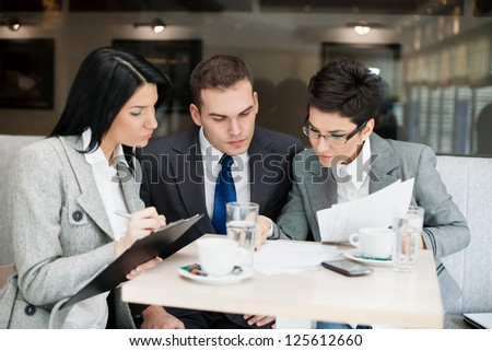 Young businesspeople having a business meeting at coffee table - stock photo