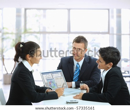Young businesspeople having a business meeting at coffee table in office lobby, using laptop computer. - stock photo