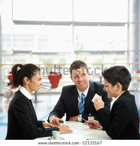 Young businesspeople having a coffee break, sitting at table in office lobby. - stock photo