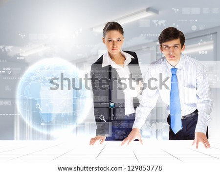 young businesspeople looking at high-tech image of globe - stock photo