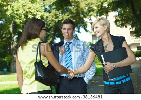 Young businesspeople meeting in park, shaking hands. - stock photo
