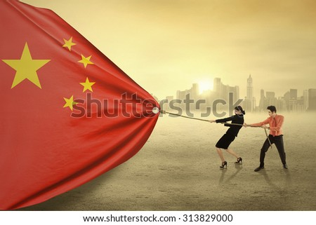 Young businesspeople pulling a chinese flag together, shot outdoors - stock photo