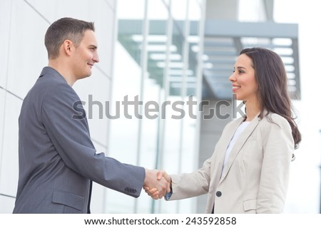 Young businesspeople shaking hand in front of the office building - stock photo