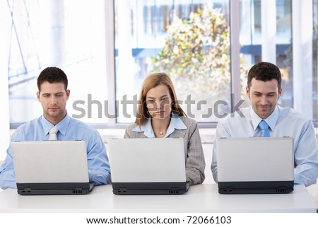 Young businesspeople sitting at desk in bright office, busy by working on laptop.? - stock photo