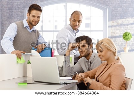 Young businesspeople sitting at desk, using laptop computer, working in team. - stock photo