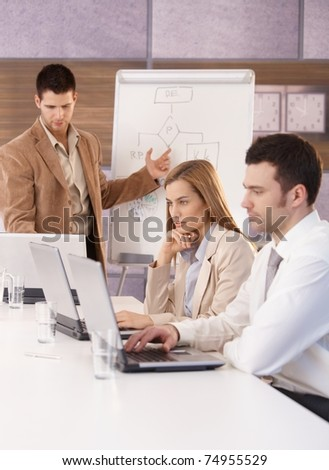 Young businesspeople sitting at meeting, using laptop and whiteboard.? - stock photo