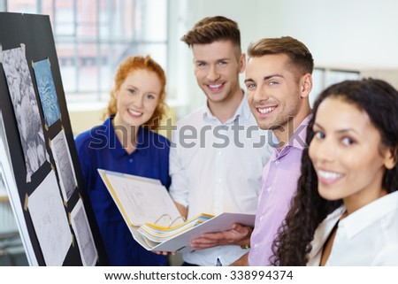 young businesspeople standing at the whiteboard looking at camera with a smile - stock photo