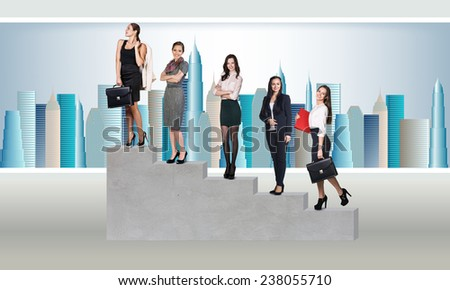 Young businesspeople standing on stairs over a city background - stock photo