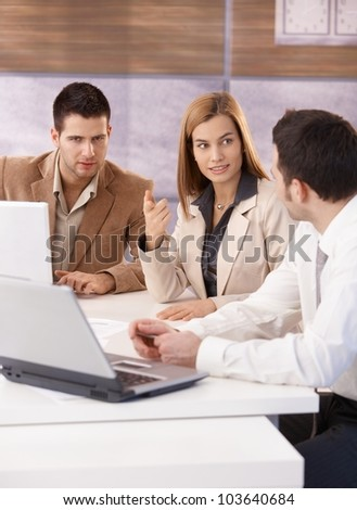 Young businesspeople teamworking in meeting room, using laptop, having discussion.