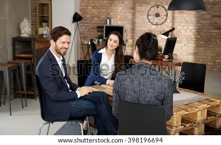 Young businesspeople working in startup office, talking around pallet table. - stock photo