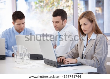 Young businesspeople working on laptop sitting in meeting room. - stock photo