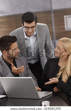 Young businesspeople working together in office, sitting at desk, using laptop computer . - stock photo