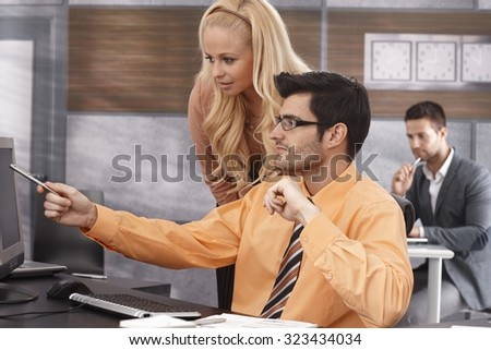 Young businesspeople working together in office, using computer. - stock photo
